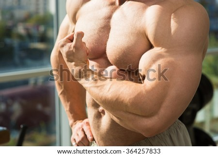 Muscular torso and arms. Bodybuilder with huge muscles. Strong man's torso. Picture of muscular torso, arms and abs. - stock photo