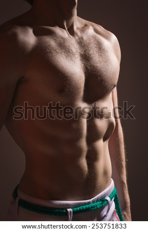 Muscular torso of athletic man over dark background - stock photo