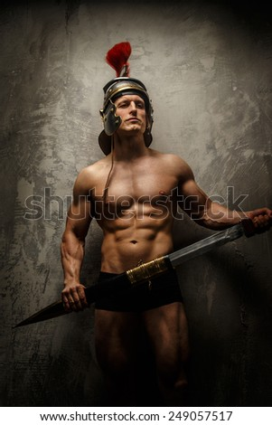 Muscular warrior with sword and helmet posing in front of concrete wall - stock photo