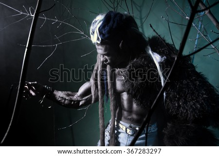 Muscular werewolf among the branches of the tree. Gothic image of scary diabolical creatures for Halloween - stock photo