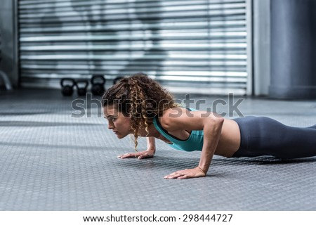 Muscular woman doing pushups at the crossfit gym - stock photo