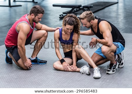 Muscular woman having a muscle injury sitting on ground - stock photo