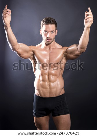 muscular young bodybuilder showing off his perfect fit body - stock photo