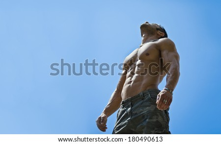 Muscular young male bodybuilder shirtless looking up in the sky, seen from below - stock photo