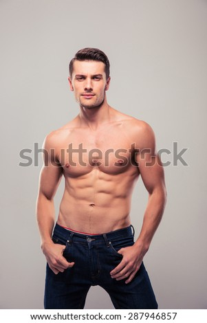 Muscular young man in jeans looking at camera over gray background - stock photo