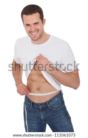 Muscular young man measuring waist. Isolated on white - stock photo