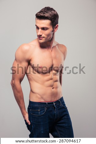 Muscular young man posing over gray background. Looking away - stock photo