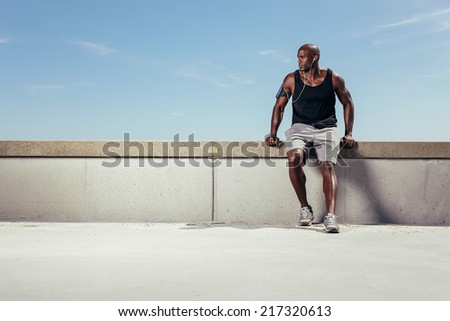 Muscular young man relaxing on embankment looking away copyspace. African male athlete wearing earphones outdoors. Male runner relaxing. - stock photo