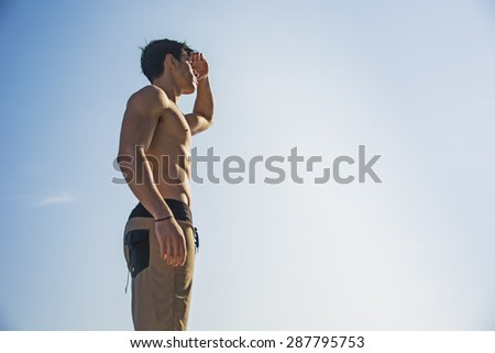 Muscular young man shirtless peering and looking far, shielding eyes with one hand, against the sky, seen from below perspective - stock photo