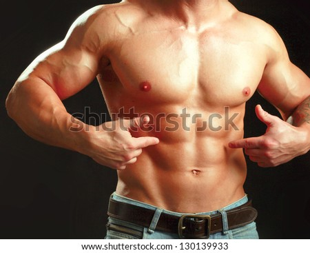 Muscular young man  showing abs. - stock photo
