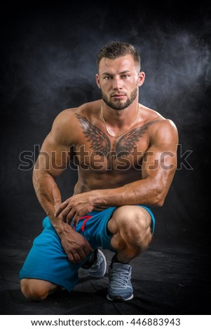 Muscular young man standing shirtless - stock photo