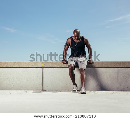 Muscular young man taking breath after his run. African male athlete outdoors with copy space. Male runner relaxing after running exercise. - stock photo