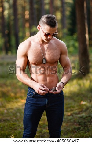 Muscular young man with sunglasses in a forest. - stock photo