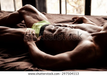 Muscular young sexy guy lies on the bed without clothes in underwear - stock photo