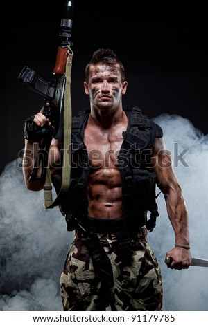 Muscular young sexy naked soldiers with knives and weapons in army clothes in the smoke - stock photo