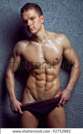 Muscular young sexy wet man takes off her underwear - stock photo