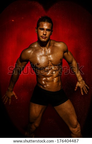 Muscular young sexy wet naked handsome man posing. Valentine's day. - stock photo