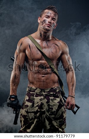 Muscular young wet sexy naked soldiers with weapons in army clothes in the smoke and camouflage paint - stock photo