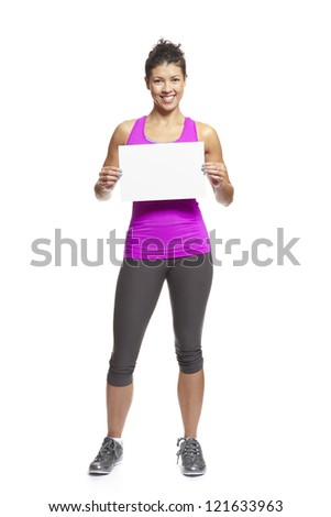 Muscular young woman in sports outfit holding blank card on white background - stock photo