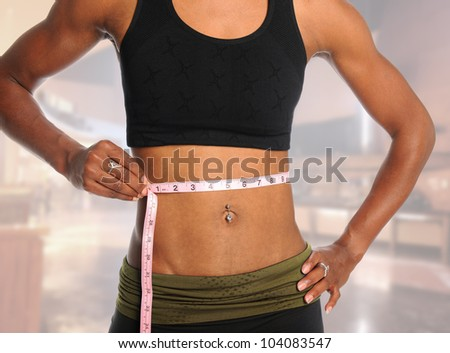 Muscular young woman measuring waist with tape isolated over blurred background - stock photo