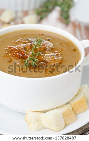 Mushroom cream soup with croutons and thyme in a bowl close-up vertical - stock photo