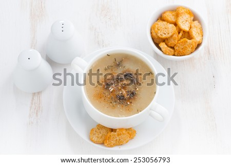 mushroom cream soup with croutons on white table, horizontal, top view, close-up - stock photo