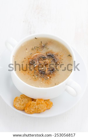 mushroom cream soup with croutons on white wooden table, vertical, top view - stock photo