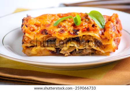 Mushroom lasagna piece on plate, selective focus - stock photo