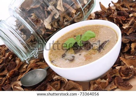 Mushroom soup in a bowl, decorated with basil, with dried mushrooms surrounding it and some in a jar, and an antique spoon - stock photo