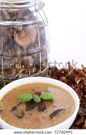 Mushroom soup in a bowl, decorated with basil, with dried mushrooms surrounding it and some in a jar - stock photo