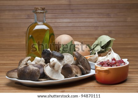 Mushrooms, eggs, ham and olive oil to cook a good menu. - stock photo