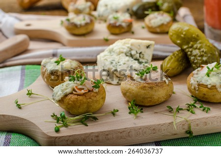 Mushrooms stuffed with blue cheese, microgreens on top, simple delicious food snack - stock photo