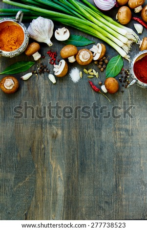 Mushrooms with herbs and spices on dark wooden table. Background with space for text. Vegetarian food, health or cooking concept. - stock photo