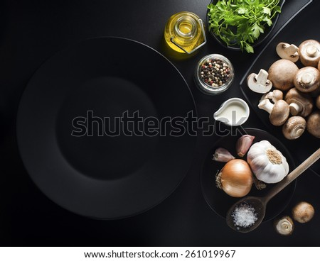 Mushrooms with ingredients on a black background - stock photo