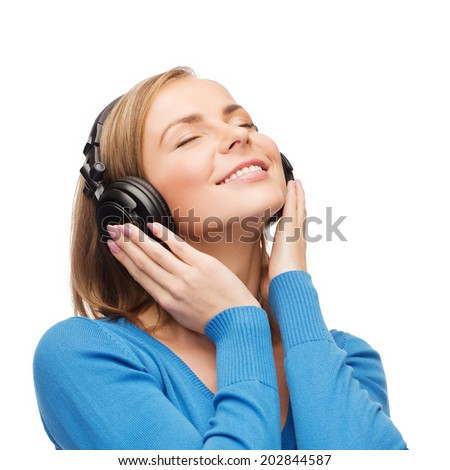 music and technology concept - smiling young woman with closed eyes listeting to music with headphones - stock photo