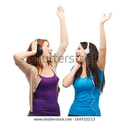 music and technology concept - two laughing teenagers with headphones dancing - stock photo