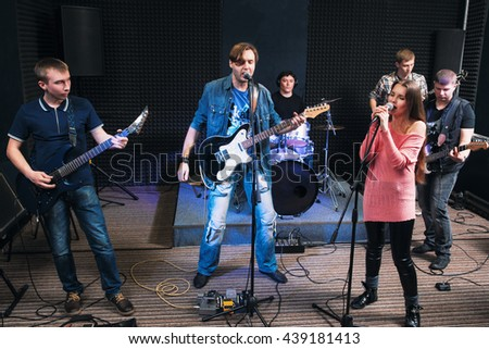 Music band alive performance on stage. Two vocalists sing, other member play on their musical instruments. Music group play their song. - stock photo