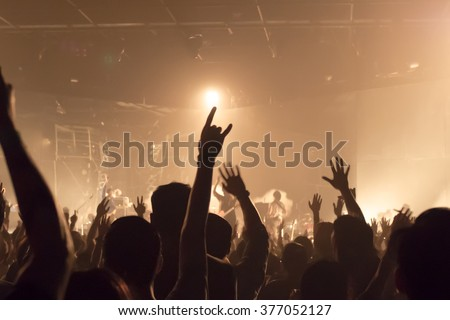 Music band crowds raising hands up in the air (very shallow depth of field) - stock photo