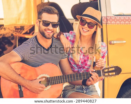 Music break during road trip. Handsome young man sitting in minivan and playing guitar while his cheerful girlfriend bonding to him and smiling - stock photo