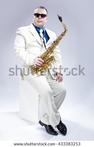 Music Concept and Ideas. Full Length Portrait of Caucasian Musician With Alto Saxophone Posing In White Suit and Black Sunglasses Against White Background. Vertical Image Orientation - stock photo