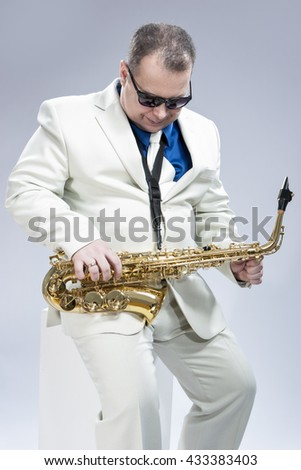 Music Concept and Ideas. Handsome Caucasian Musician with Saxophone Posing in White Suit Against Gray. Vertical Image - stock photo