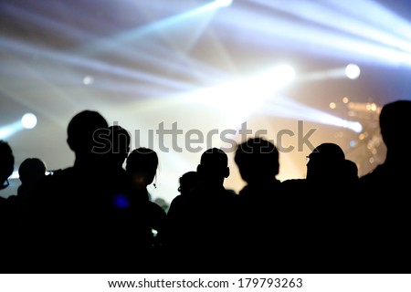 Music concert with stage and audience at live concert cheering with bright light at stage area as free space for text. - stock photo