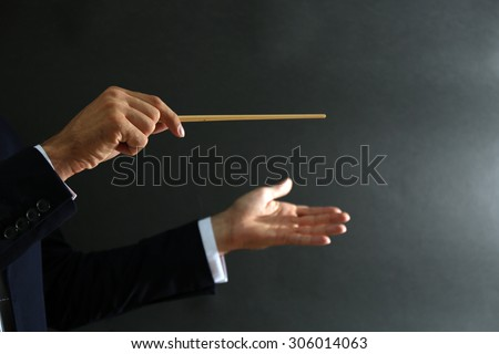 Music conductor hands with baton on black background - stock photo