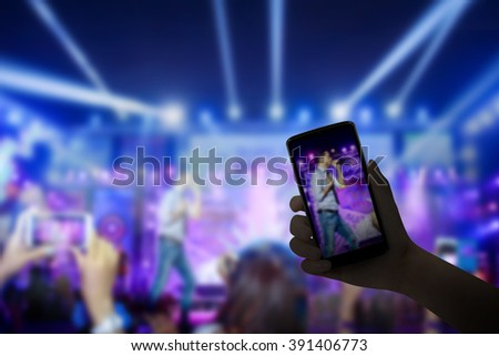 Music fans takes smartphone video records at concert, live concert, music festival, happy youth, luxury party, landscape exterior. - stock photo
