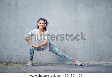 Music, fitness and lifestyle. Attractive young woman with headphones stretching on the street. - stock photo