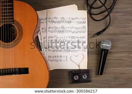 Music recording scene with classical guitar, music sheets, cassette and microphone on wooden table, closeup - stock photo
