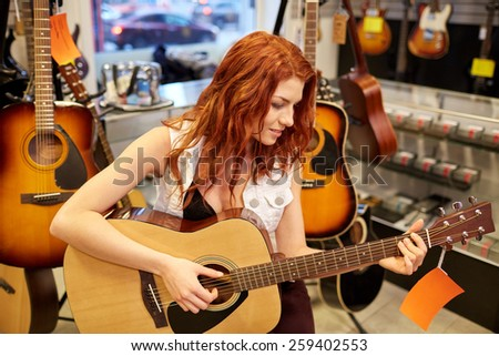 music, sale, people, musical instruments and entertainment concept - female musician or customer playing bass guitar at music store - stock photo