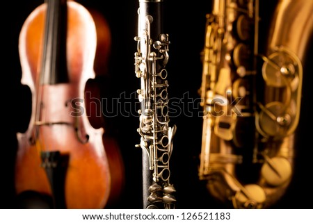Music Sax tenor saxophone violin and clarinet in black background - stock photo