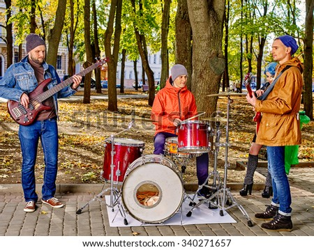Music street men performers on park autumn outdoor. - stock photo