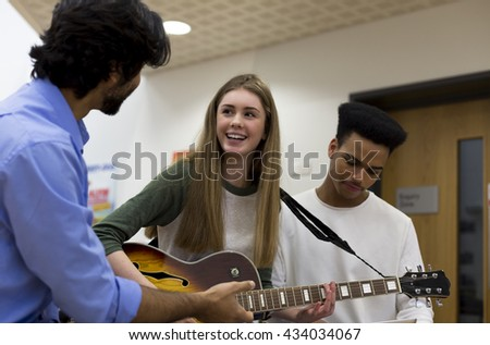Music teacher helping students learn to play guitar.  - stock photo